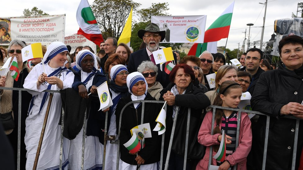 People await the arrival of Pope Francis with flags and banners