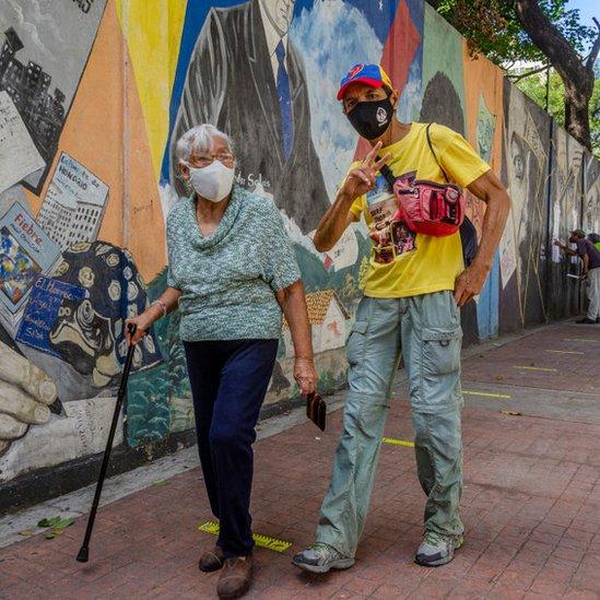 Una mujer adulta mayor caminando junto a un joven en Caracas.