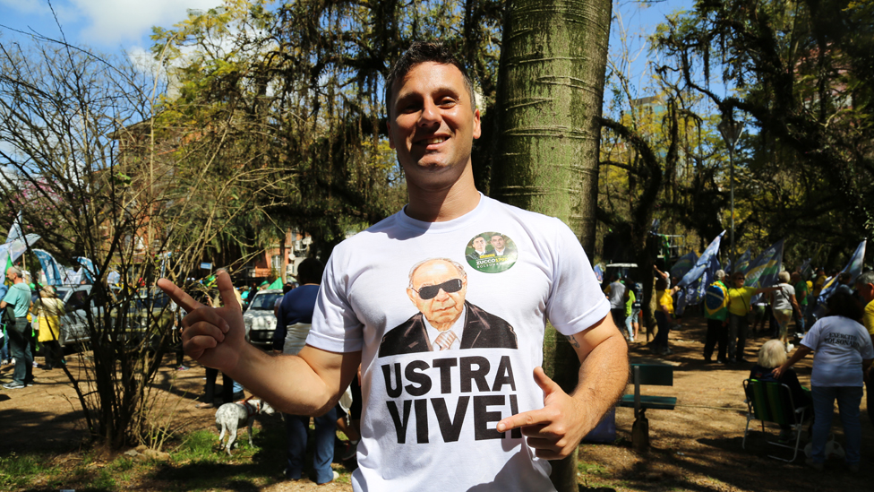 A man wears a T-Shirt with a picture of Carlos Alberto Brilhante Ustra
