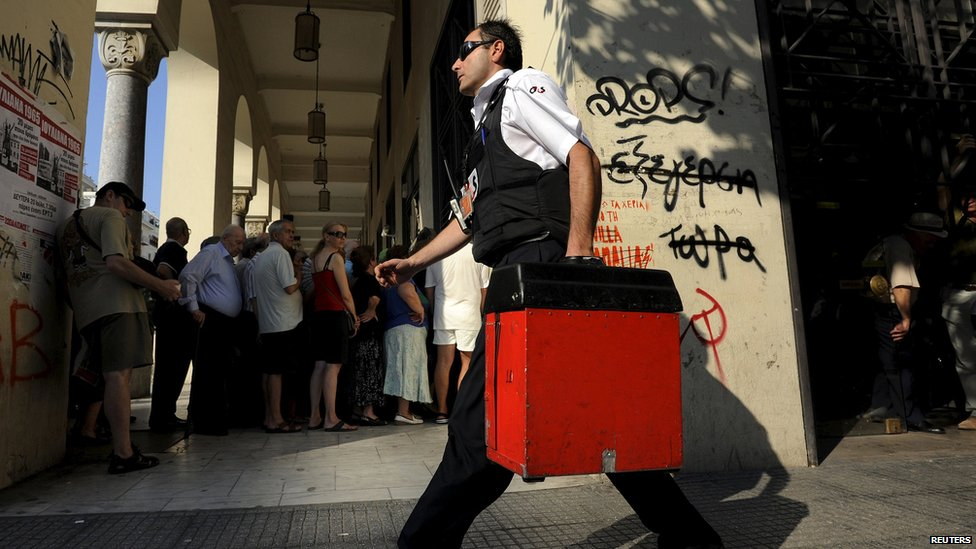 A security worker carries money outside a National Bank branch in the city of Thessaloniki, Greece (9 July 2015)