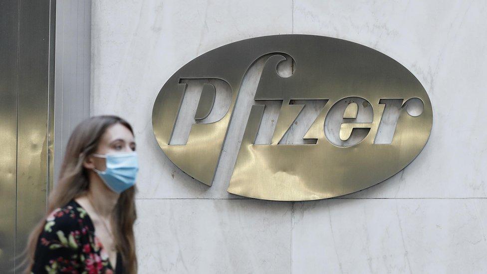 Mujer caminando frente a la marca de Pfizer.