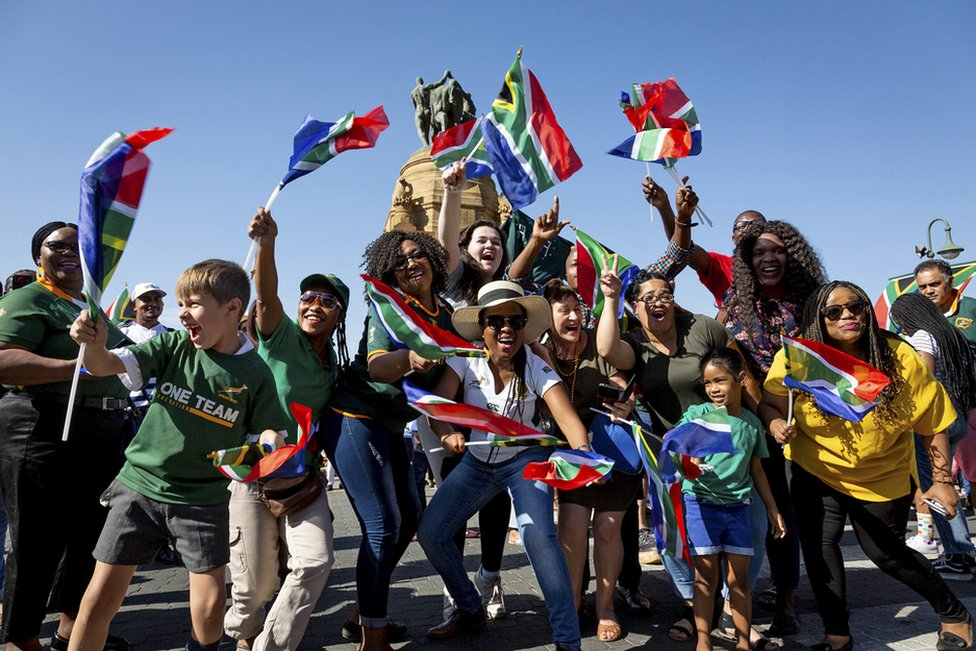 South African rugby supporters cheer for their Rugby World Cup winning national team, the Springboks, in Pretoria