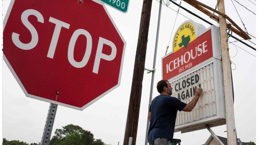 Homem muda placa para avisar que loja está fechando de novo por causa do coronavírus em Houston, no Texas