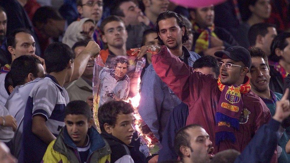 Aficionados del Barcelona queman una imagen de Figo vestido con el uniforme del Real Madrid.
