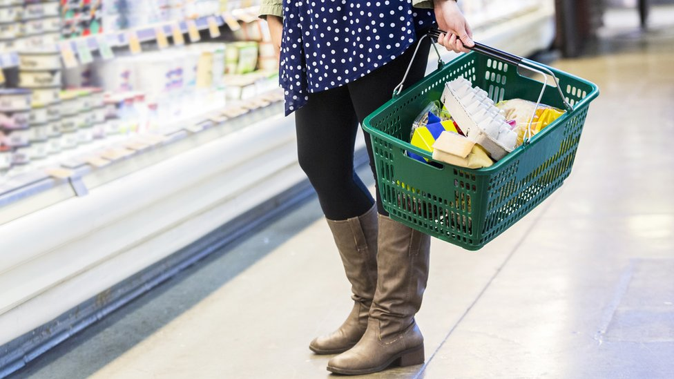 Lower half of a woman grocery shopping