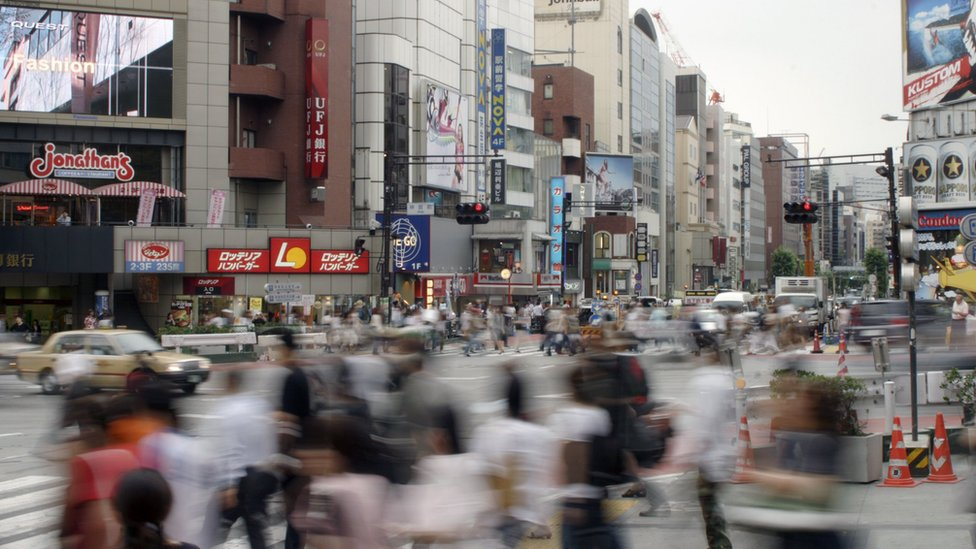 A blurred image shows the motion of busy commuters in downtown Tokyo, Japan