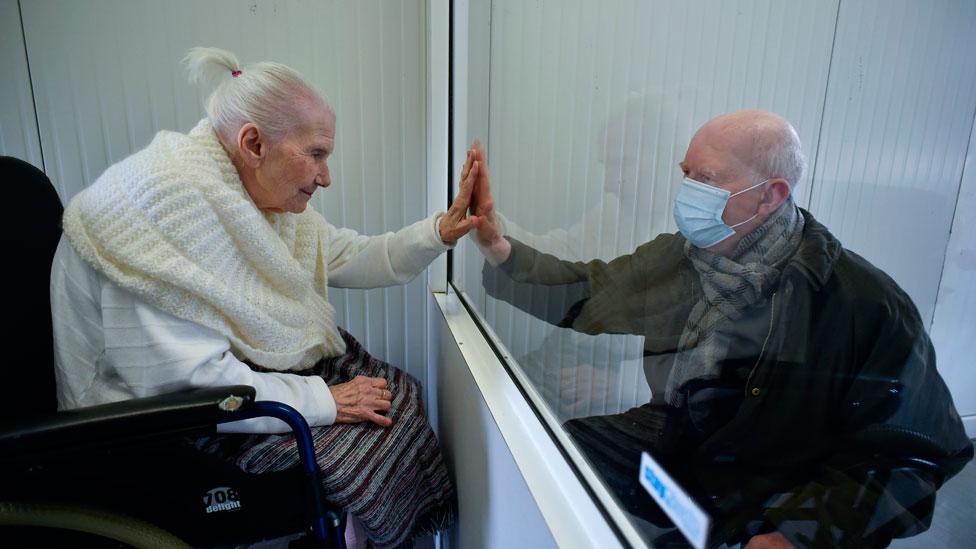Una anciana infectada con covid-19 saluda a su hijo a través de un cristal de plexiglass en Bélgica.