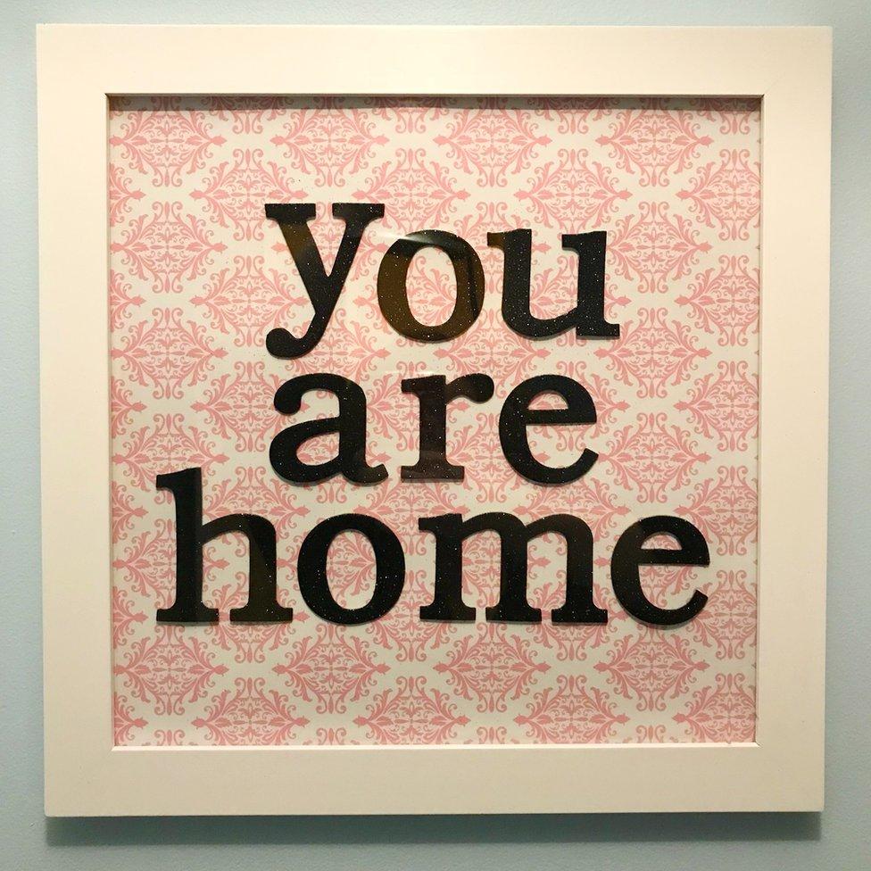 """Un cuadro con las palabras """"estás en casa""""."""