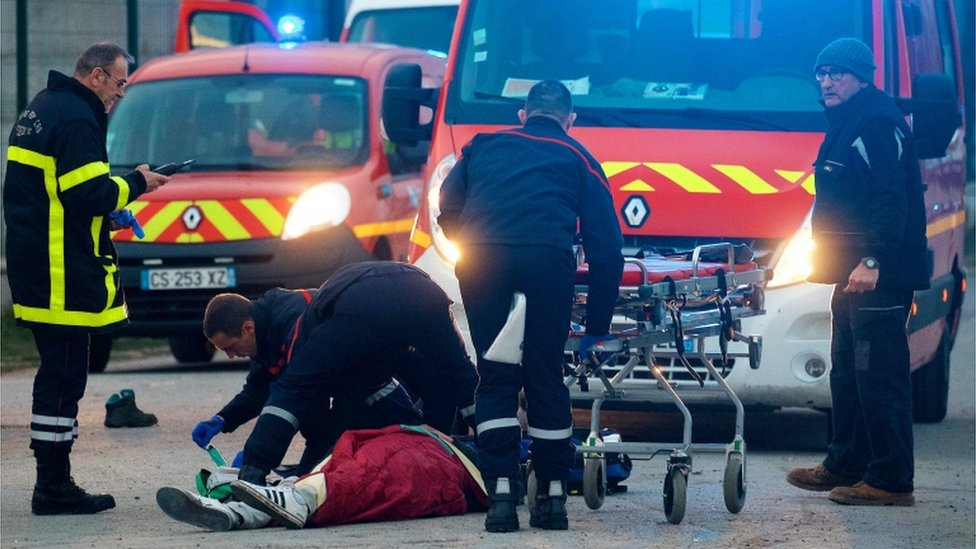 A migrant receives medical assistance by rescue workers following clashes near the ferry port in Calais, northern France, 01 February 2018.
