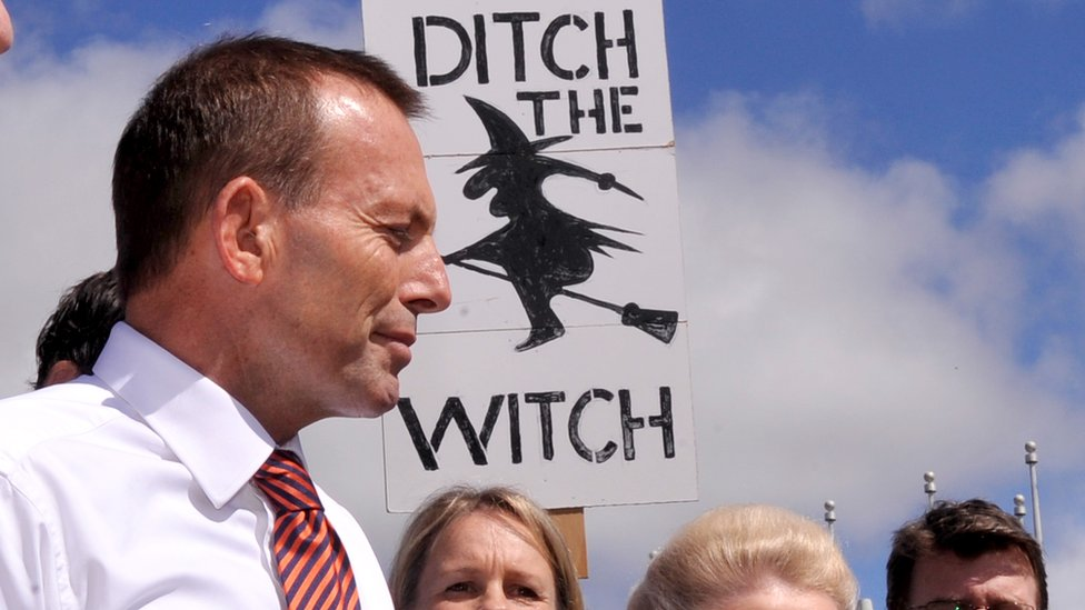 Australia's then opposition leader, Tony Abbott, stands in front of a sign being held held by a protester in 2011. The sign reads: