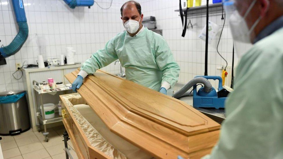 Personal forense con un ataúd.