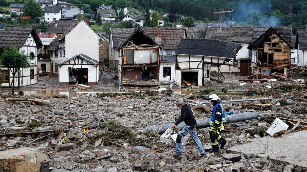 Un hombre y un bombero caminan entre los escombros, tras las fuertes lluvias en Schuld, Alemania.