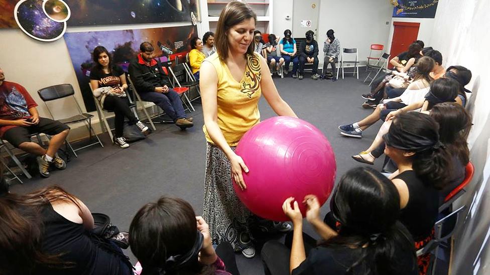 Profesora mostrando una pelota de pilates que representa al Sol