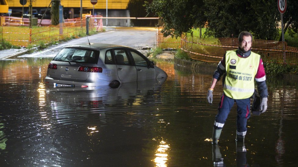An Italian policeman wades in a flooded street near an abandoned car