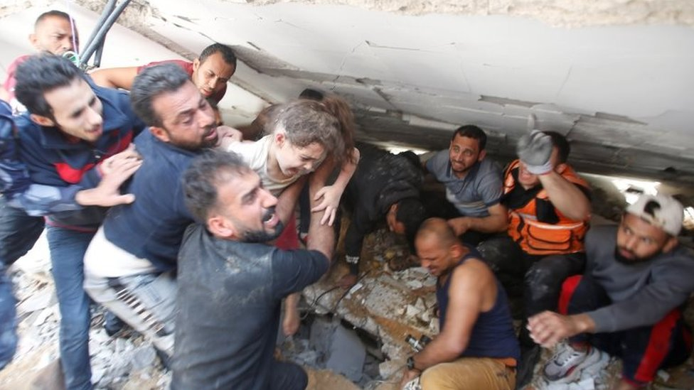 Rescuers carry a girl as they search for victims amid rubble at the site of Israeli air strikes, in Gaza City May 16, 2021