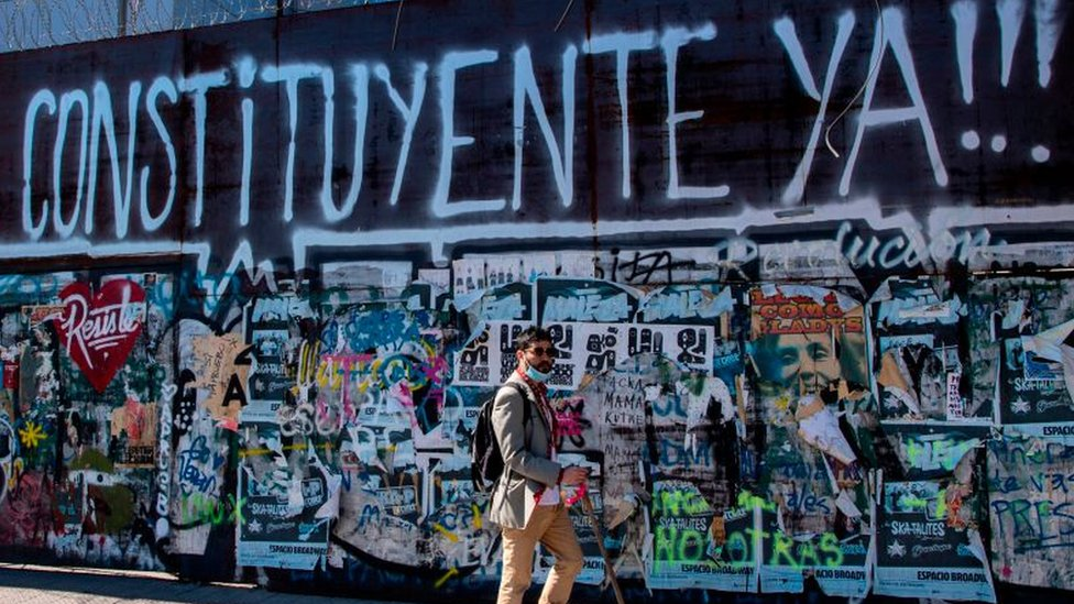 Un hombre junto a un mural con un graffiti a favor de la Constituyente en Chile.