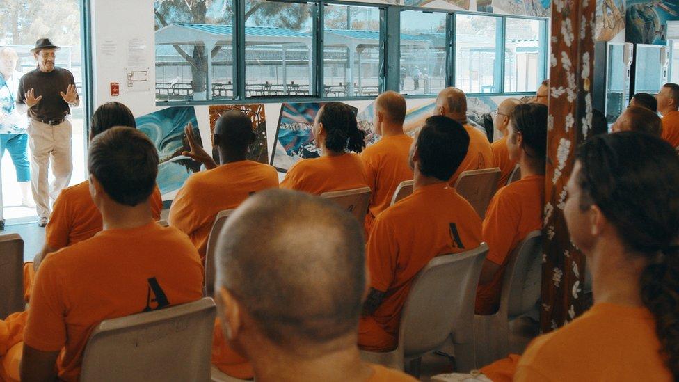U filmu, Deni se vraća iza rešetaka kao motivacioni govornik za zatvorenike