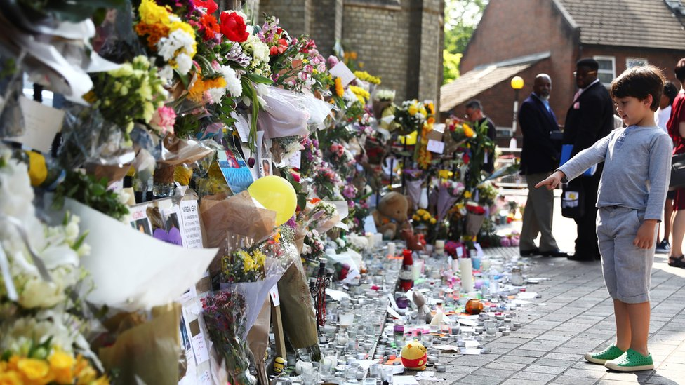 A boy points at flowers, tributes and messages left for the victims of the fire
