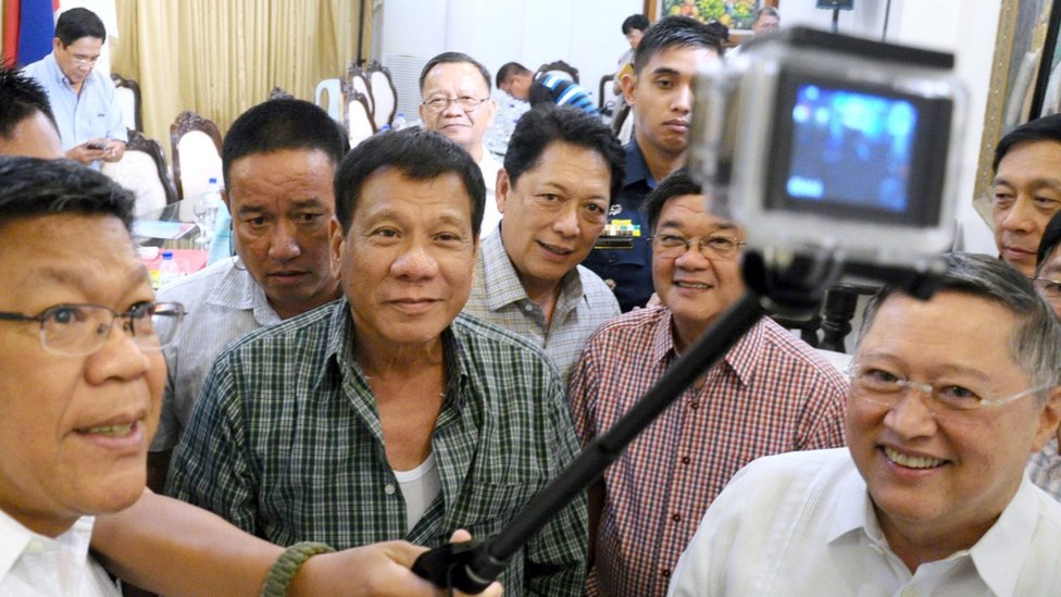 Filipino President-elect Rodrigo Duterte (centre), surrounded by a large group of male cabinet members, posing for a selfie in Davao City on 31 May 2016.