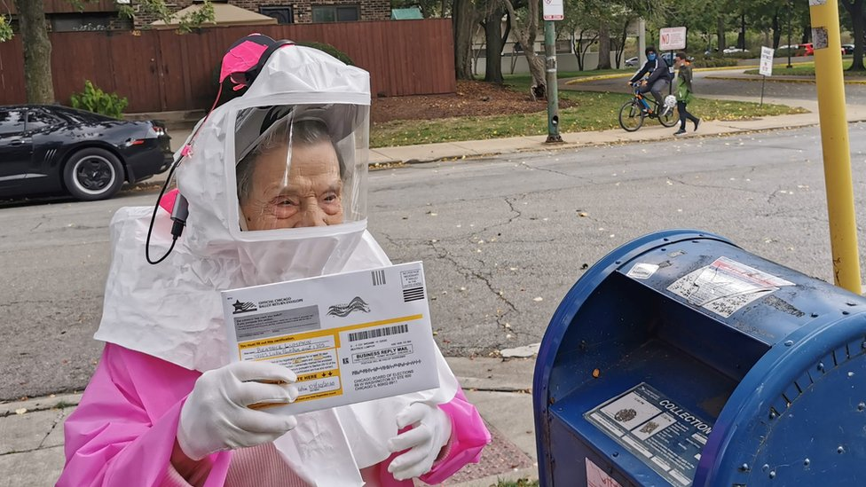 An elderly woman in a protective hood prepared to post her ballot in a mail box