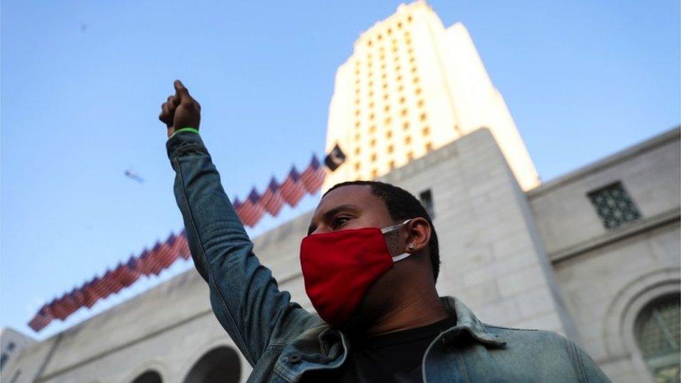 當示威者聚集在洛杉磯市政廳前時,一名男子舉起拳頭