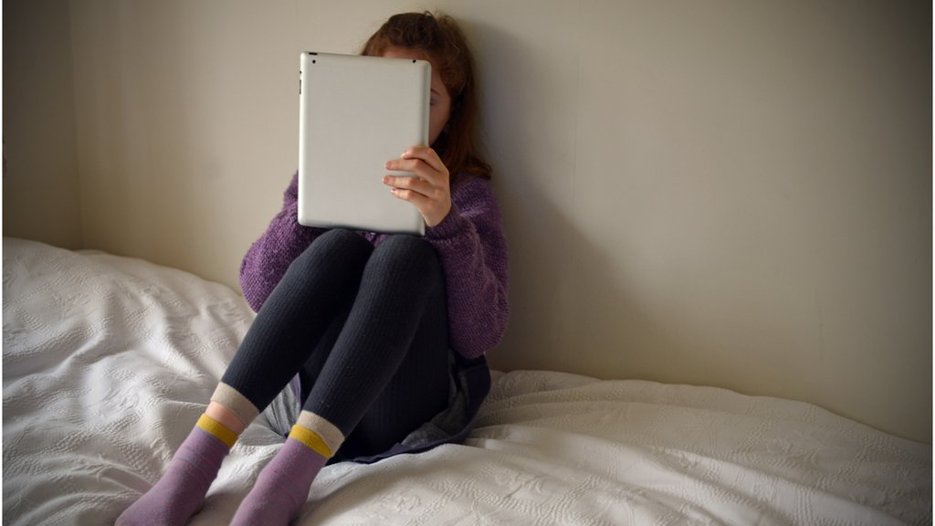 Child on bed with laptop
