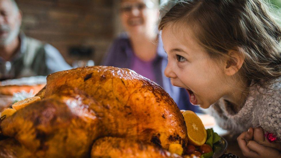 Una niña queriendo dar un mordisco a un pavo asado.