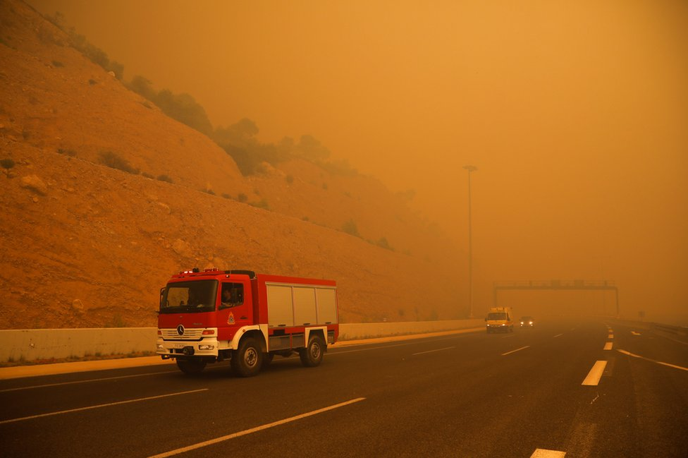 Firefighters are seen amid smoke as a wildfire burns in Kineta, near Athens