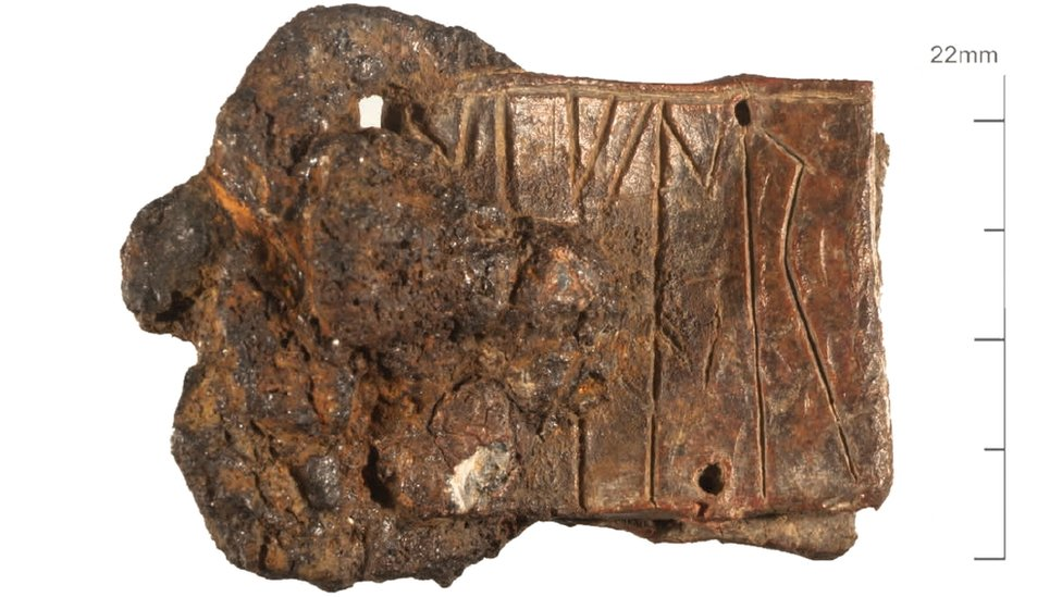 A buckle plate fashioned from a reused lead strip inscribed with runes