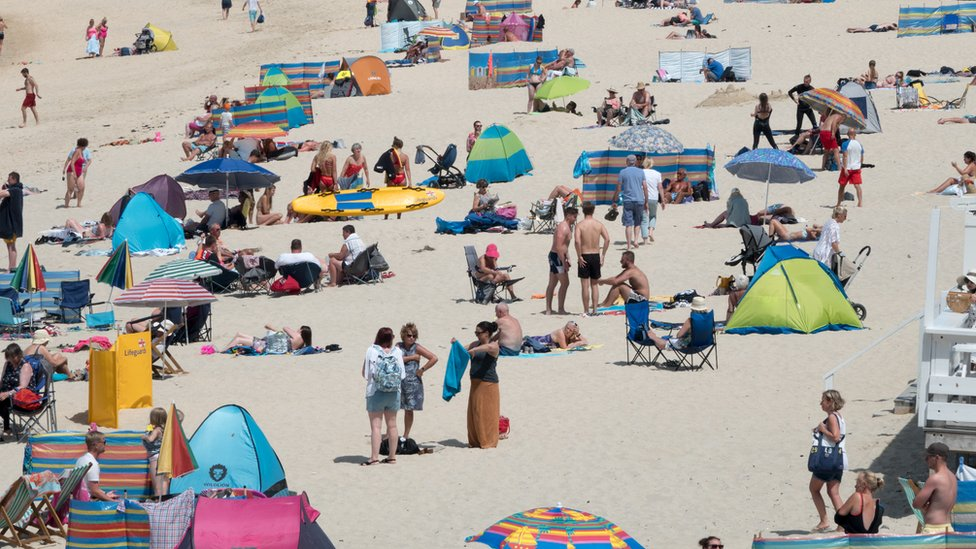 People enjoy the fine weather as they gather on Porthmeor Beach in St Ives on June 27, 2018 in Cornwall, England
