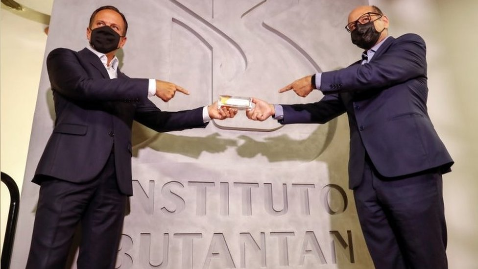 João Doria e Dimas Covas seguram uma CoronaVac com o nome do Butantan atrás