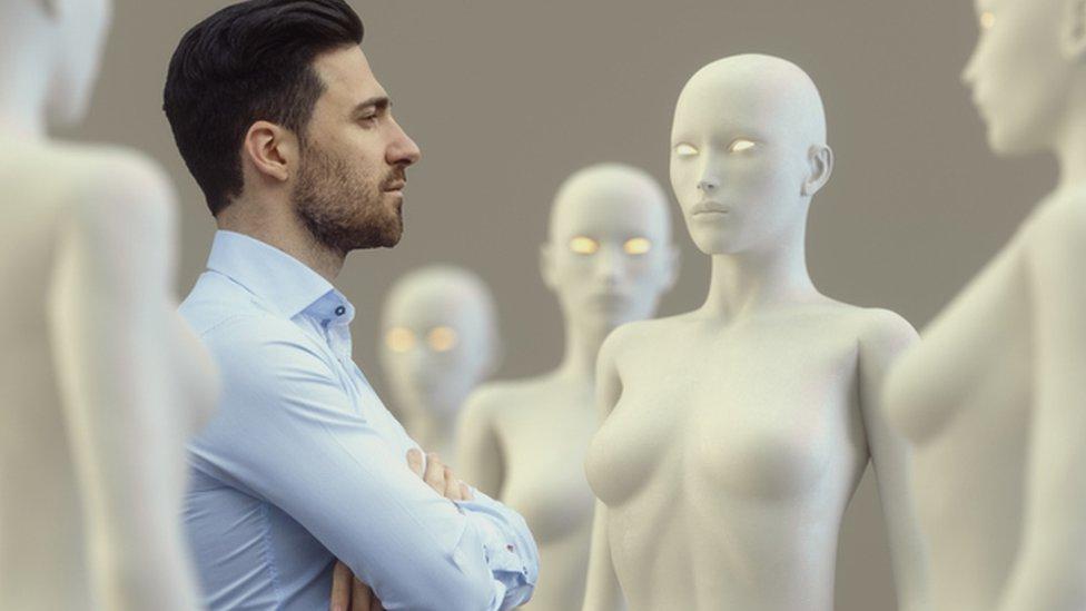 Hombre rodeado por robots de apariencia femenina.