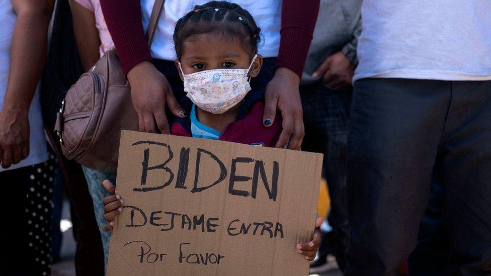 Dareli Matamoros, una niña de Honduras, sostiene un cartel pidiendo al presidente Biden que la deje entrar durante una manifestación de migrantes exigiendo políticas migratorias más claras de Estados Unidos, en el puerto de cruce de San Ysidro en Tijuana, estado de Baja California, México el 2 de marzo de 2021