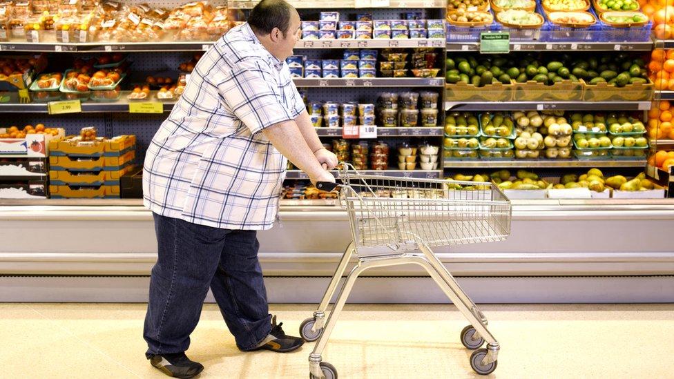 Homem obeso fazendo compras em supermercado