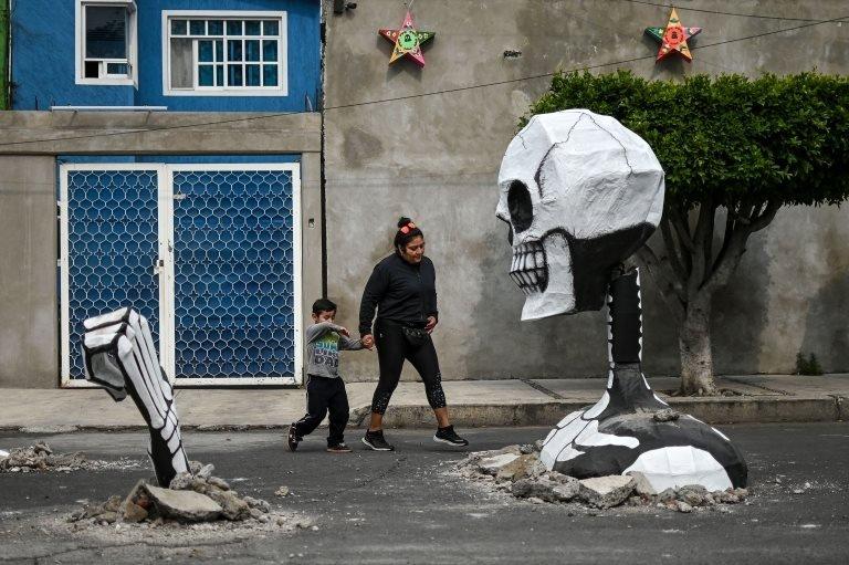سيدة و طفلها يسيران أمام الهيكل العظمي العملاق في مكسيكو سيتي