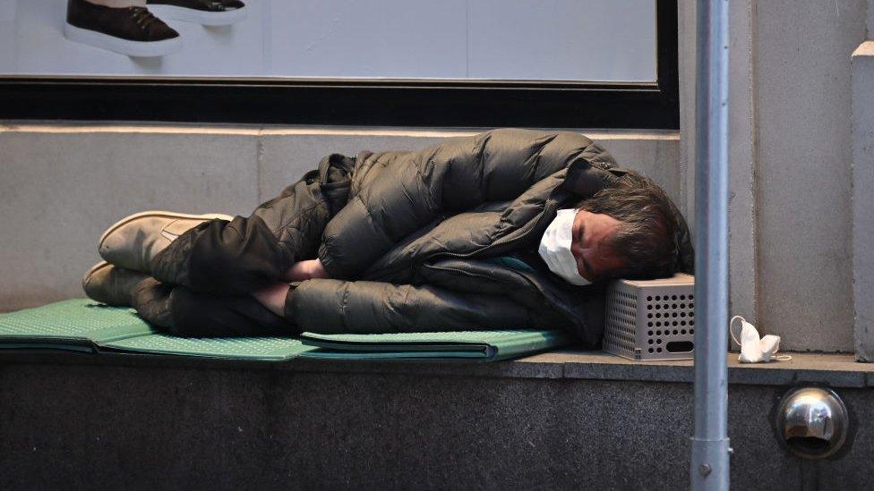 Una persona sin hogar duerme en la acera de la ciudad de Daegu.
