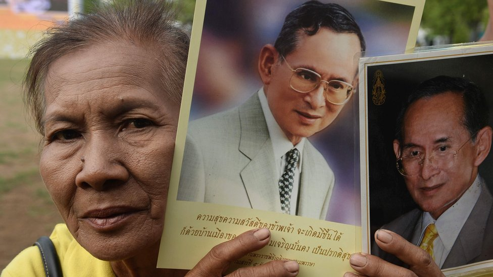 "A woman holds up images of Thailand""s King Bhumibol Adulyadej to celebrate the 70th anniversary of his reign in Bangkok on June 9, 2016."
