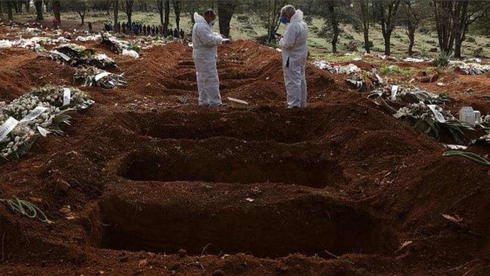 Trabalhadores com equipamentos de proteção cuidam de cova em cemitério