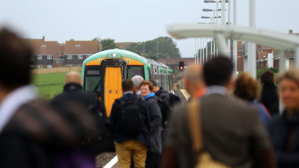 People standing on a train station platform with a train visible nearby