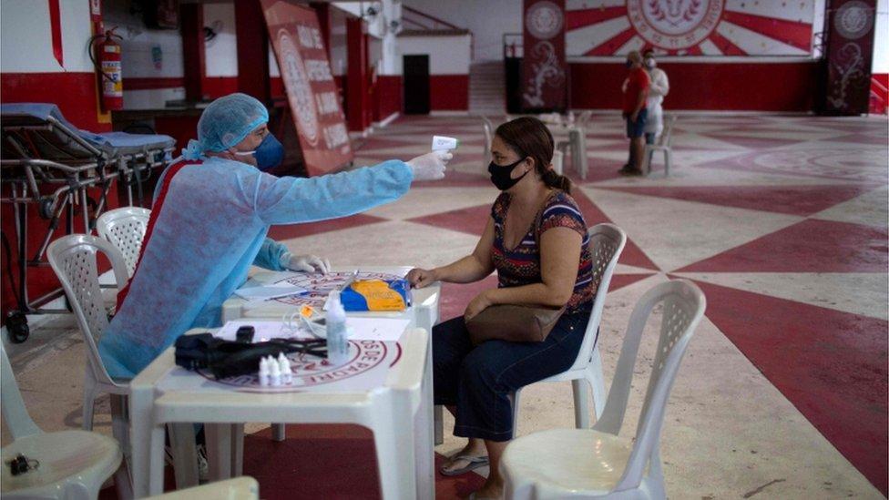 طبيب يتحقق من درجة حرارة امرأة تعاني من الأعراض في ريو دي جانيرو، البرازيل، في 24 مايو/أيار