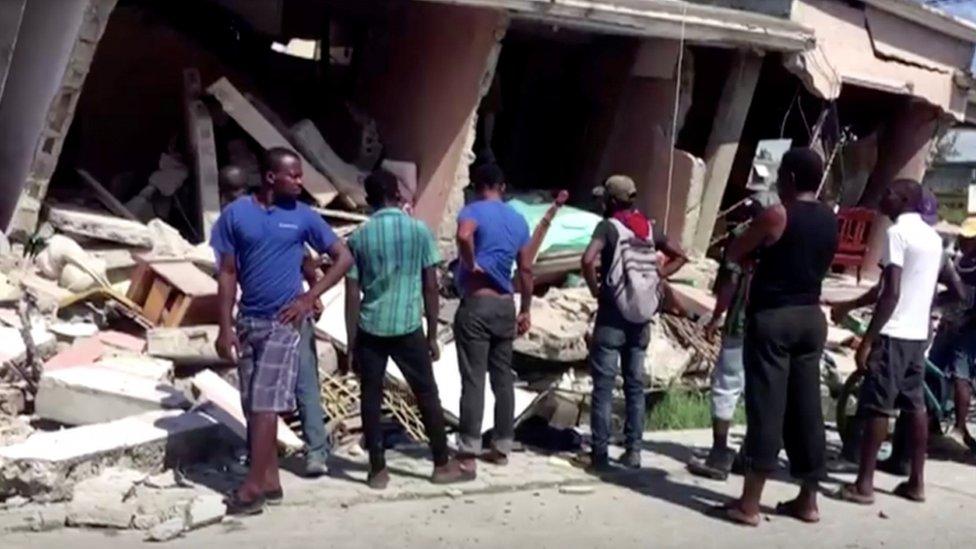 Personas observando un edificio derrumbado tras un terremoto, en Les Cayes, Haití.