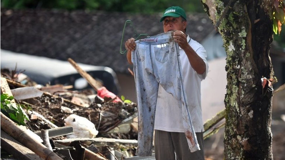 A man shows the trousers of one of the victims during the search for at people who went missing during a landslide at the Portachuelo village, in Rosas, Cauca, Colombia, 22 April 2019