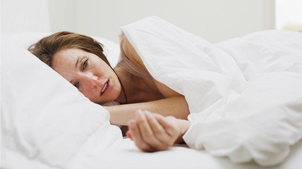 Mulher com fadiga na cama