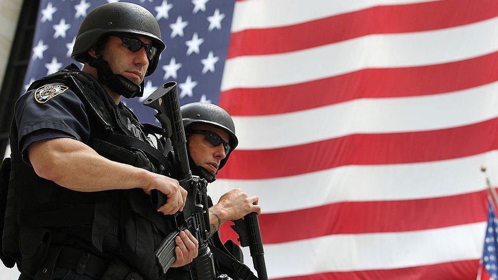 Policías en Estados Unidos, frente a una bandera de EE.UU.