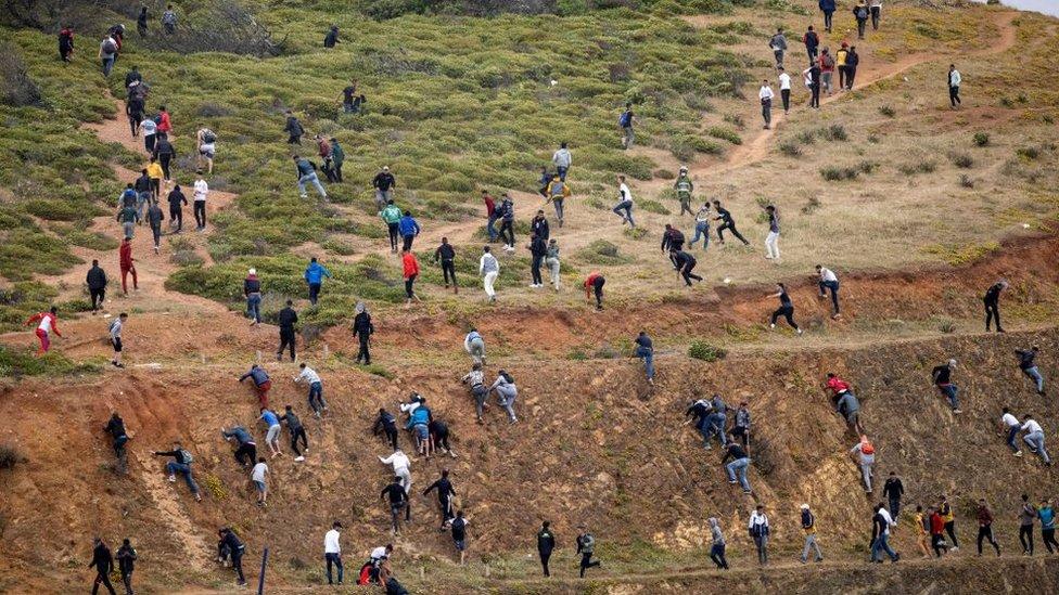 Di sisi Maroko, para migran berusaha menghindari polisi setempat untuk mencapai perbatasan dengan Spanyol.