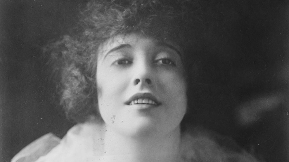 A black and white photo of Mabel as she stares directly into the camera with a small smile. Her hair is dark and curly and frames her face.
