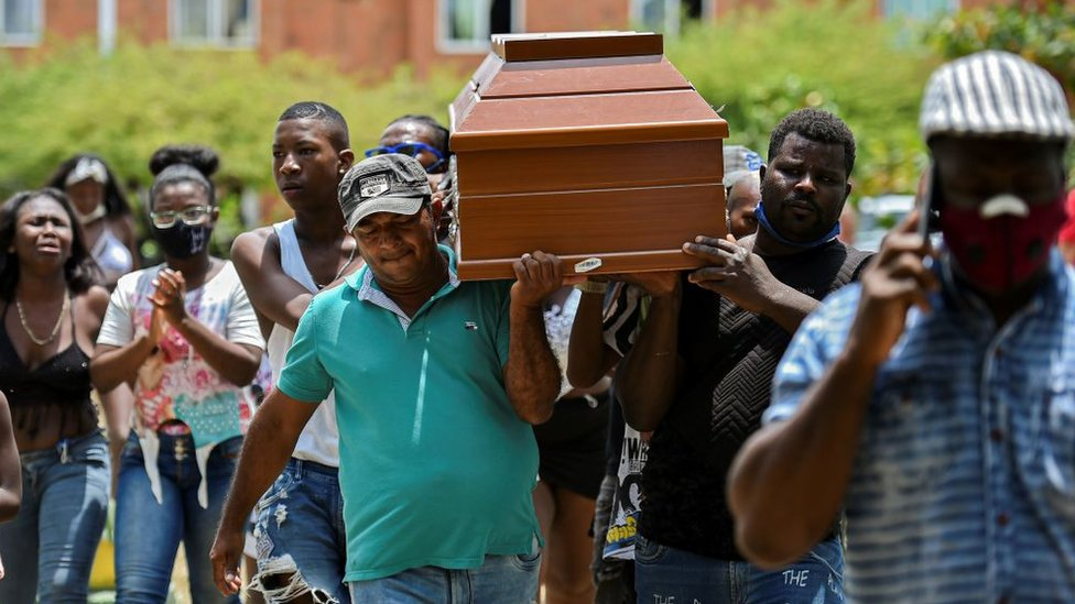 Hombres cargando uno de los ataúdes de los cinco adolescentes asesinados en Cali.