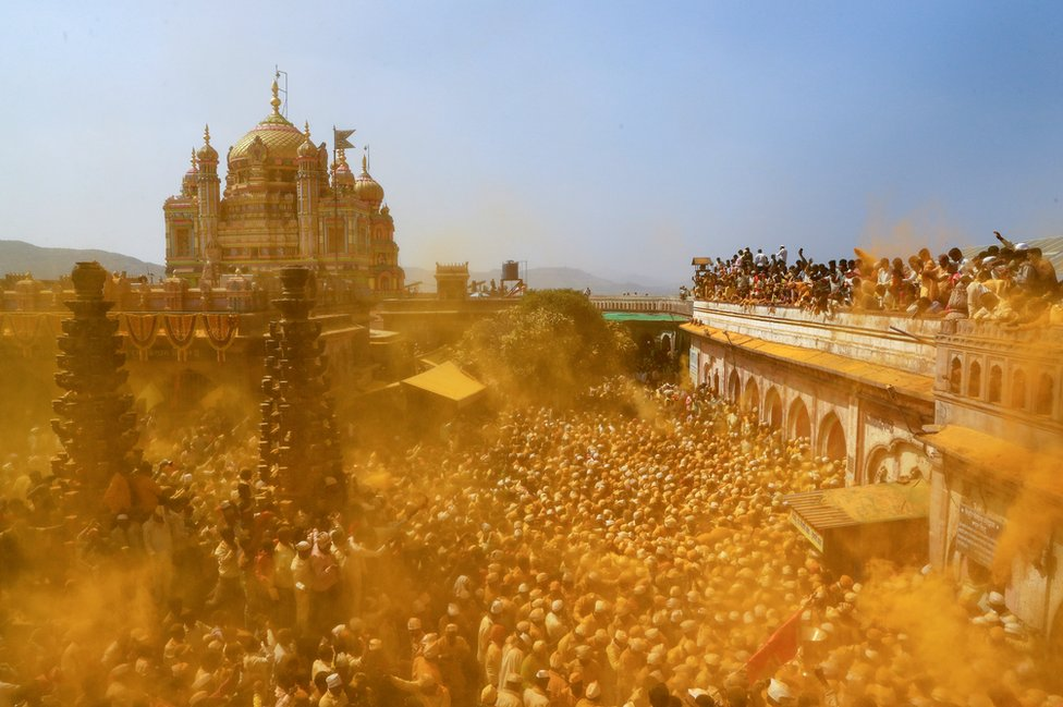Devotees throw turmeric powder as an offering to the shepherd god Khandoba as others carry a palanquin during 'Somvati Amavasya' at a temple in Jejuri, India, 4 February 2019.