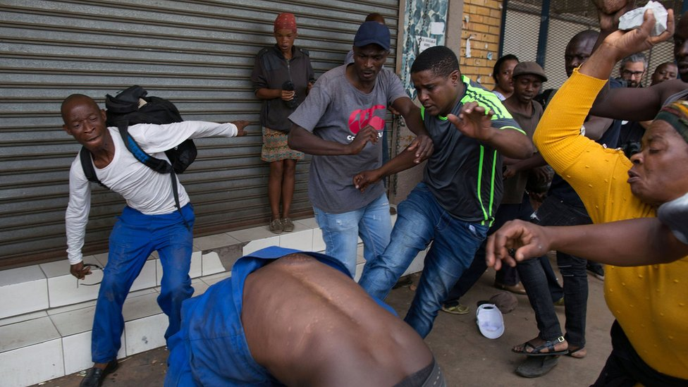 A vigilante mob attacks a Nigerian migrant outside a church in Pretoria, South Africa 18 February