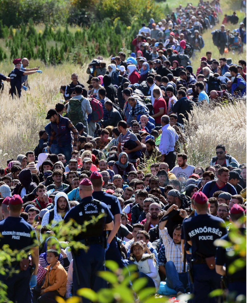 Migrants walk through the countryside after crossing the Hungarian-Croatian border near the Hungarian village of Zakany to continue their trip to the north on September 21, 2015.